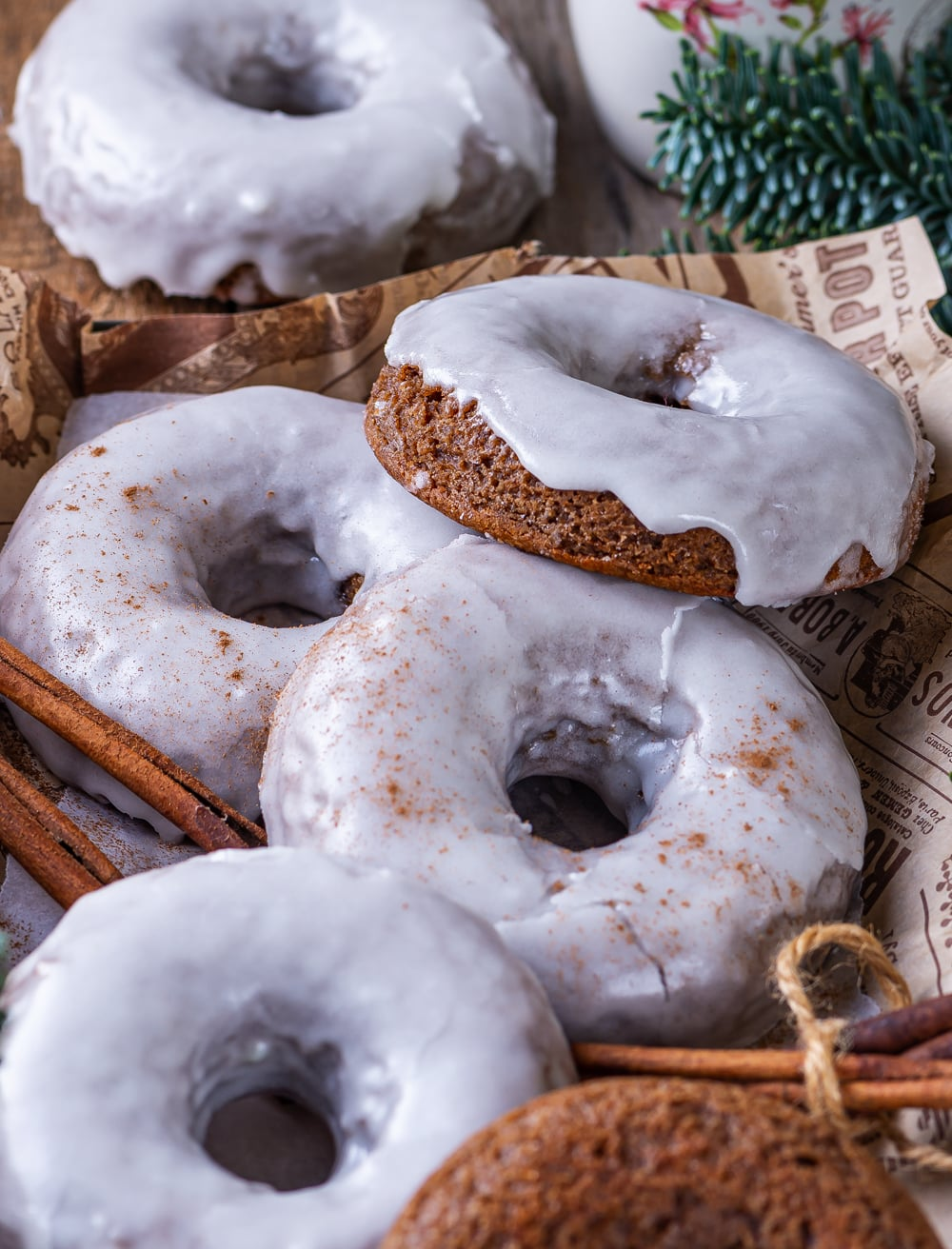 A close up of four glazed gingerbread donuts overlapping each other on a piece of paper. One glazed gingerbread donut is behind the piece of paper.