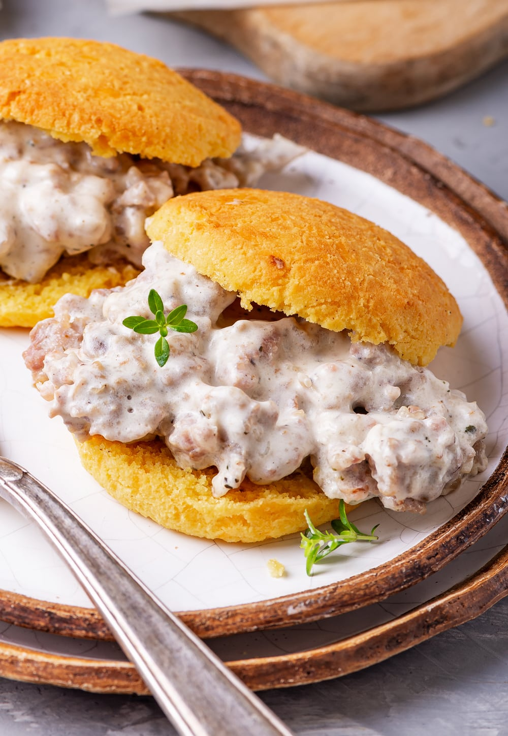A biscuit and gravy sandwich on a plate.