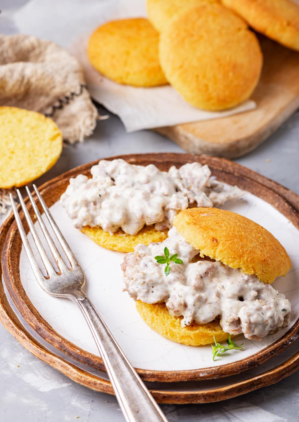 A biscuit filled with gravy and another biscuit behind it that's been topped with gravy. The biscuits are set on 2 plates that have been stacked on top of one another, and there are more biscuits on a cutting board behind the plate.