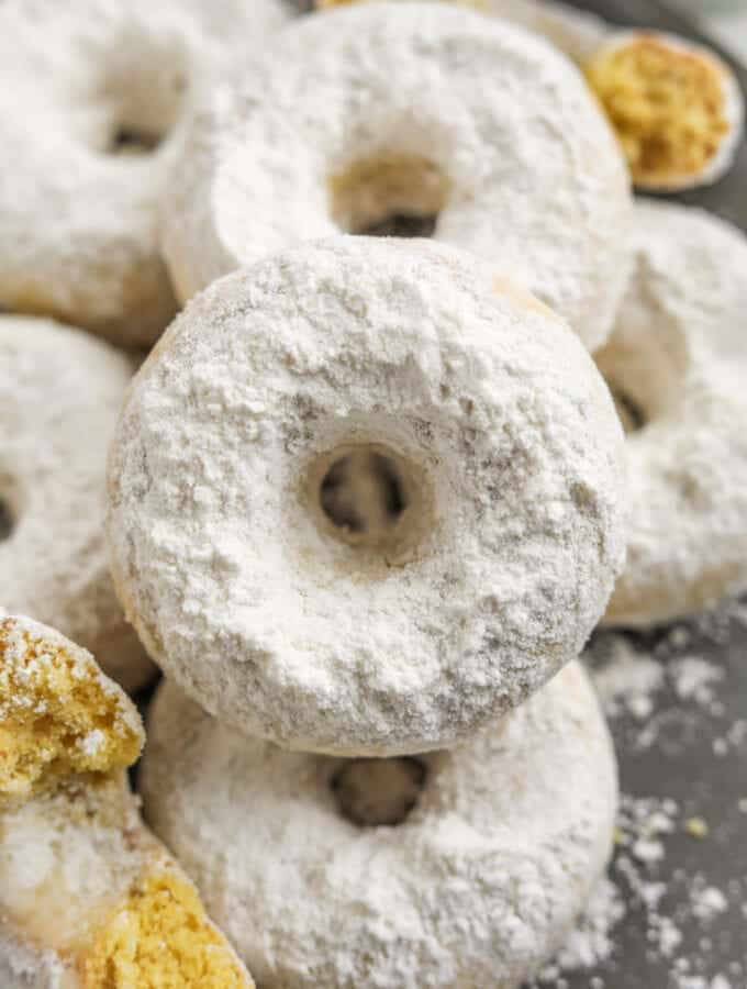 A donut set on top of other donuts. All of the donuts are covered in powdered sugar.