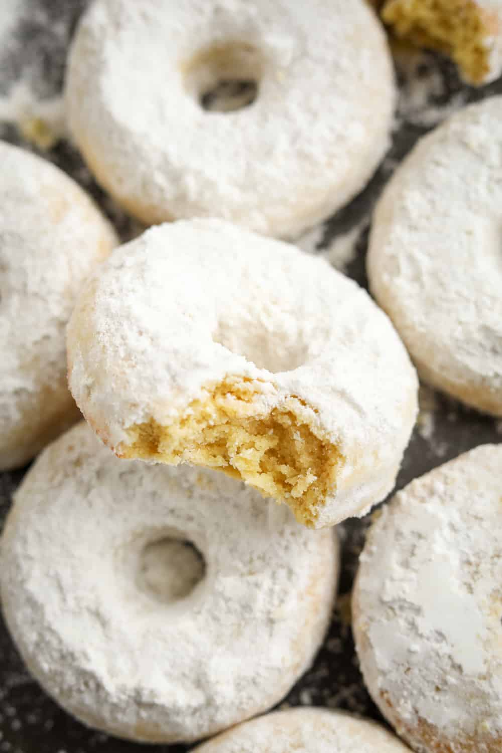 A powdered sugar donut with a bite taken out of it. The donut is stacked on top of other donuts.