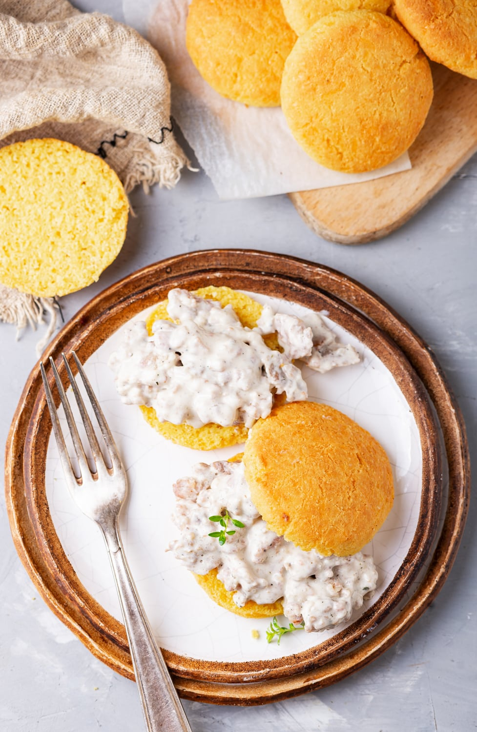 A plate with a biscuits and gravy on it. There are more biscuits scattered around the plate as well.