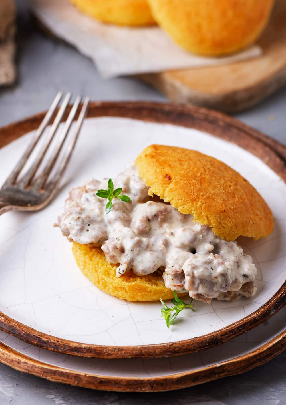 A biscuit filled with gravy on top of a plate that is stacked on top of another plate.
