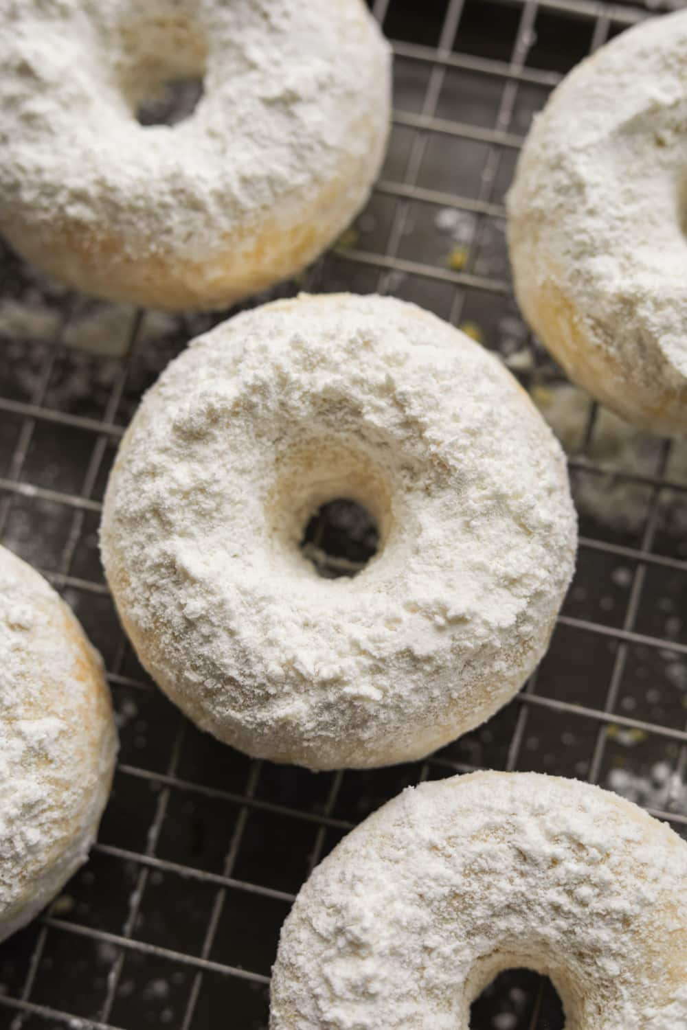 A powdered sugar donut on wire rack with other donuts around it.