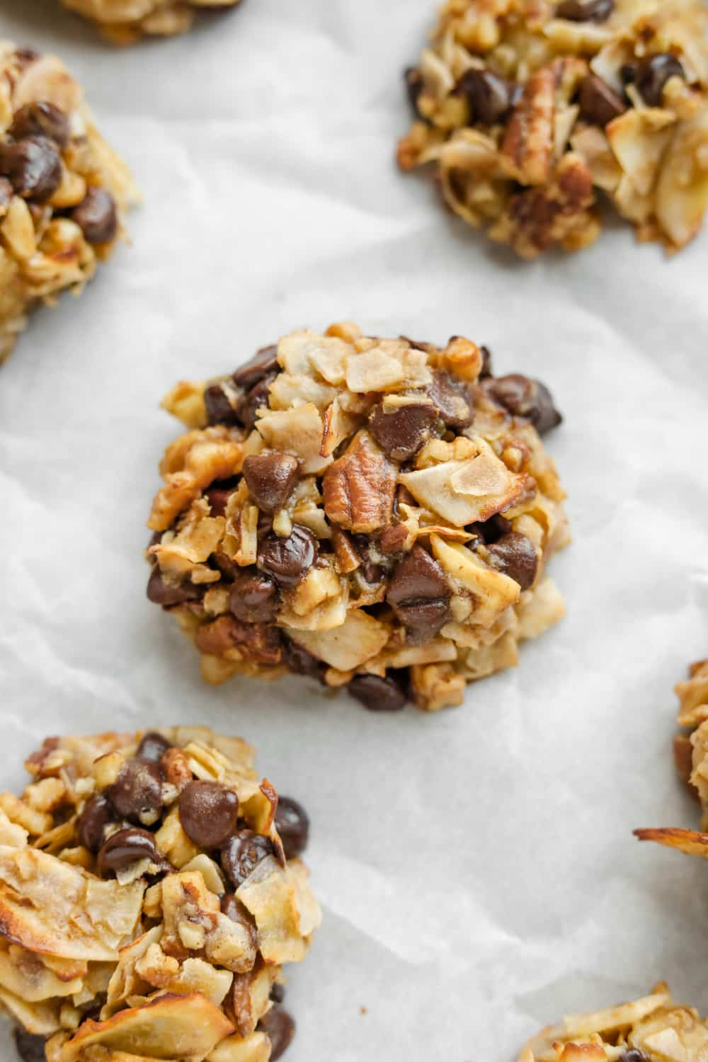 A cookie made with coconut flakes, pecans, and chocolate chips on parchment paper.