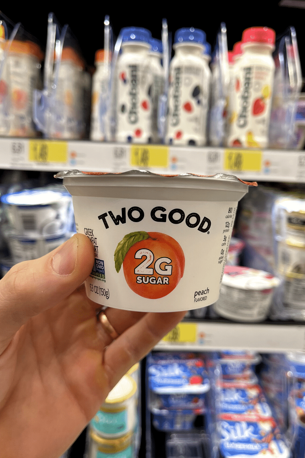A hand holding a container of low sugar peach yogurt.