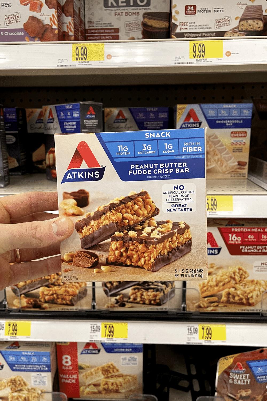 A hand holding a box of peanut butter fudge crisp bars.