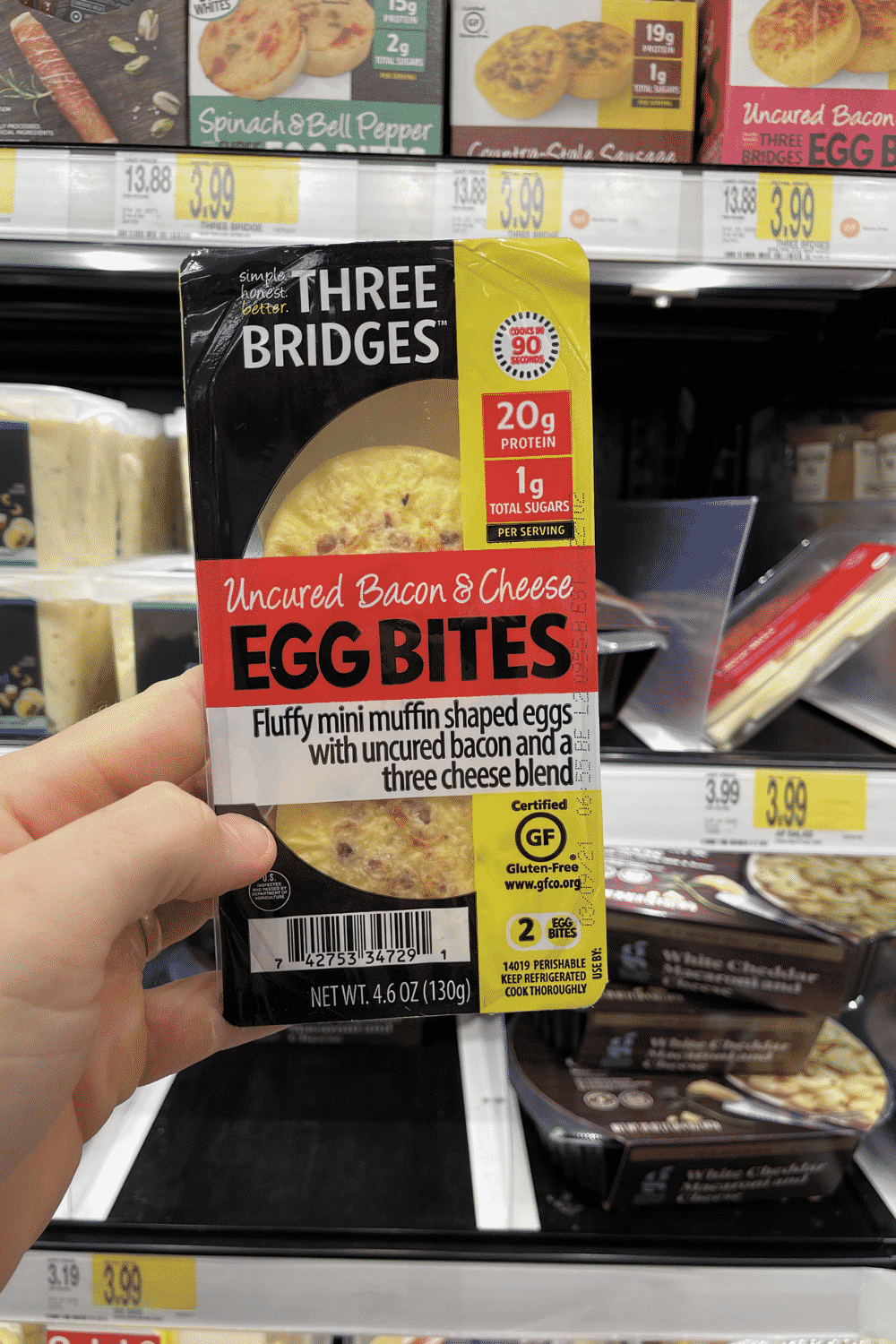 A hand holding a package of bacon and cheese egg bites.