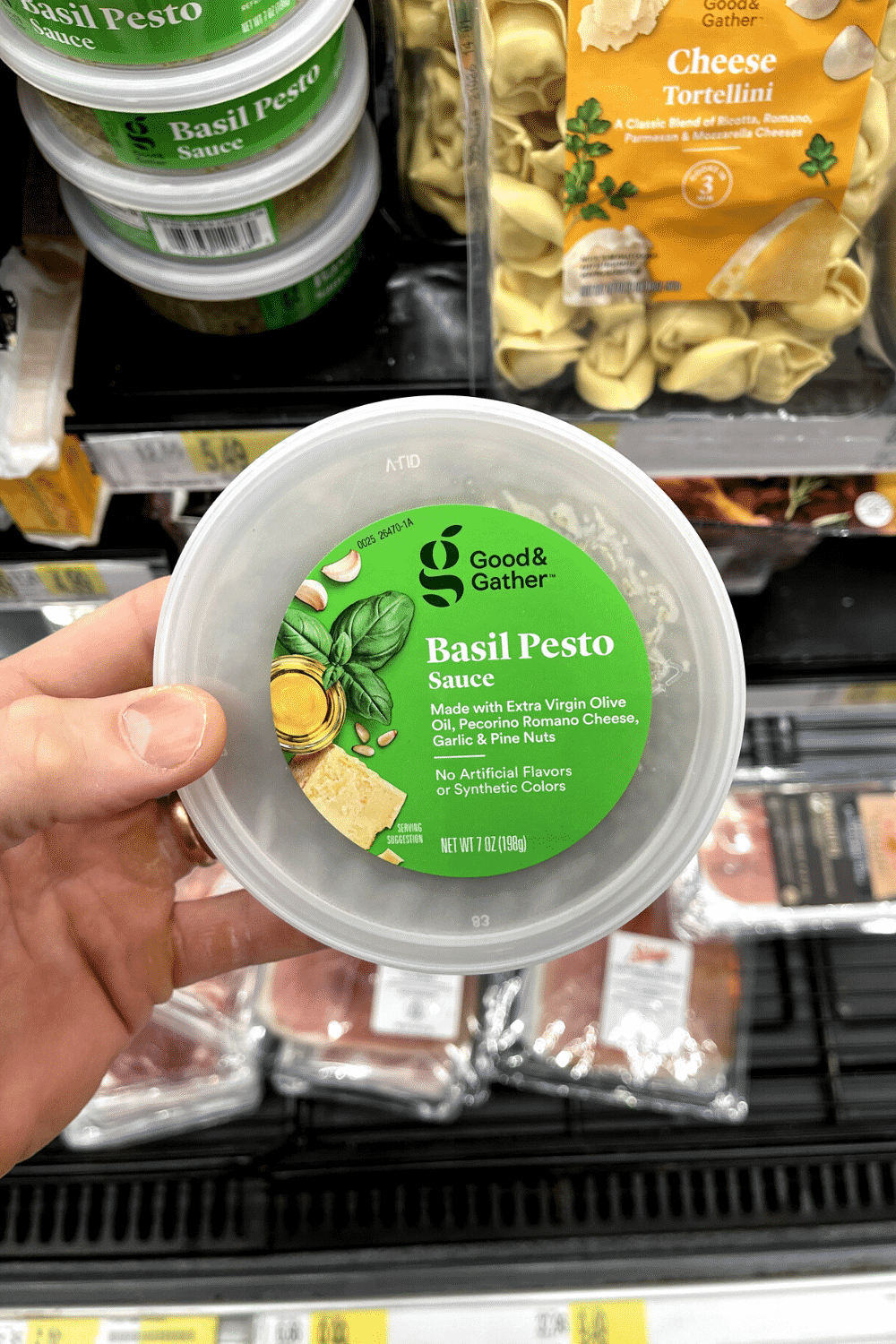A hand holding a container of basil pesto sauce.