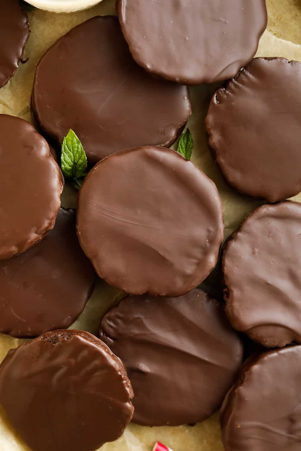 Chocolate covered cookies On a piece of brown parchment paper with mint leaves next to them.