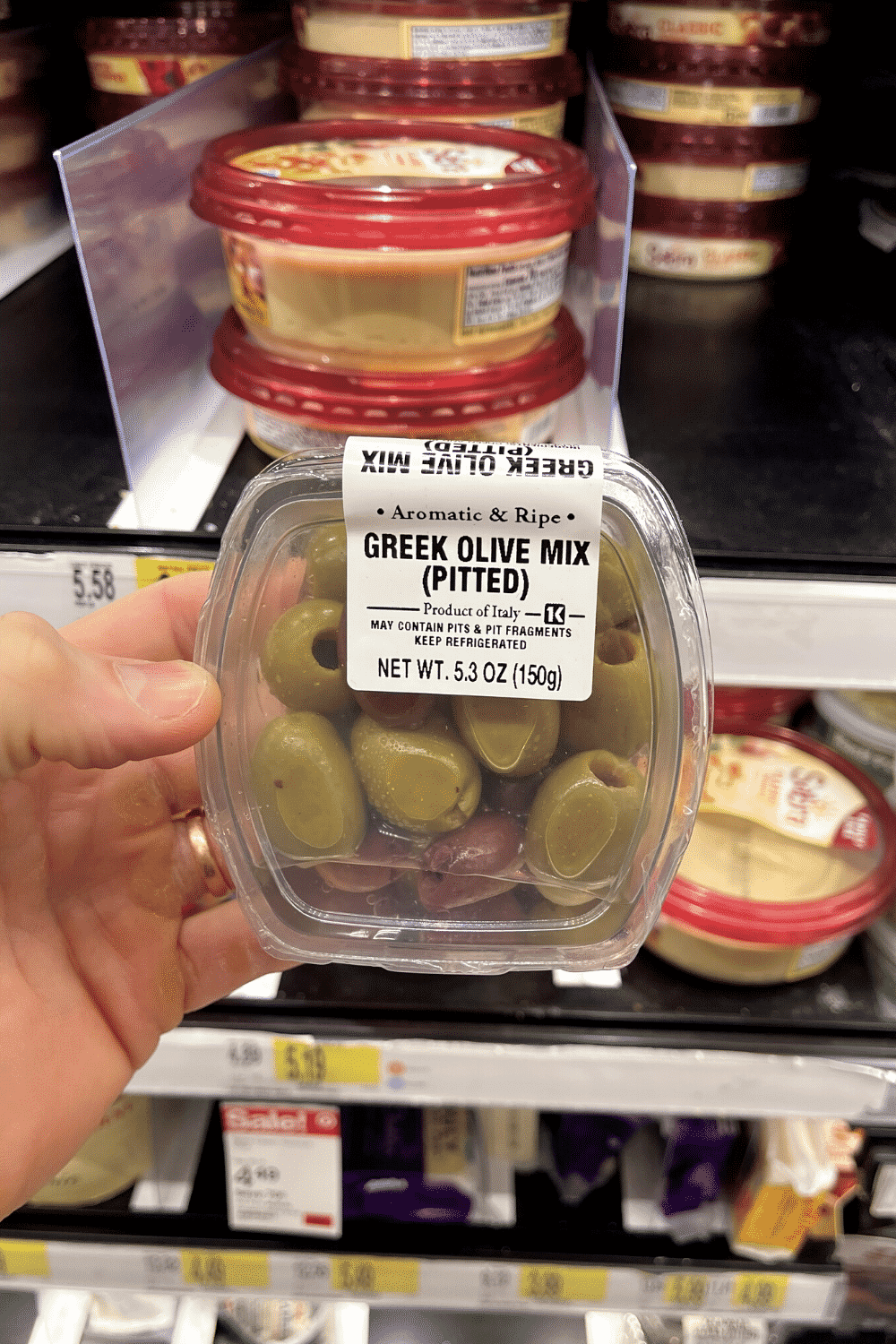A hand holding a package of Greek olives.