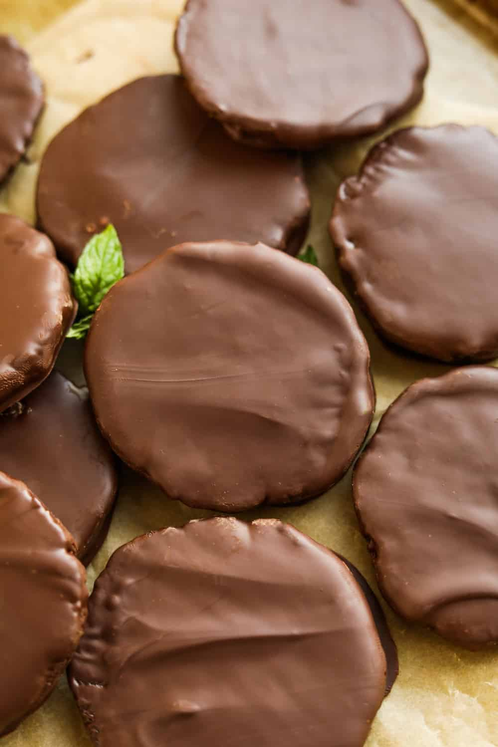 Chocolate coated cookies stacked on top of one another on a piece of brown parchment paper with a mint leaf next to them.