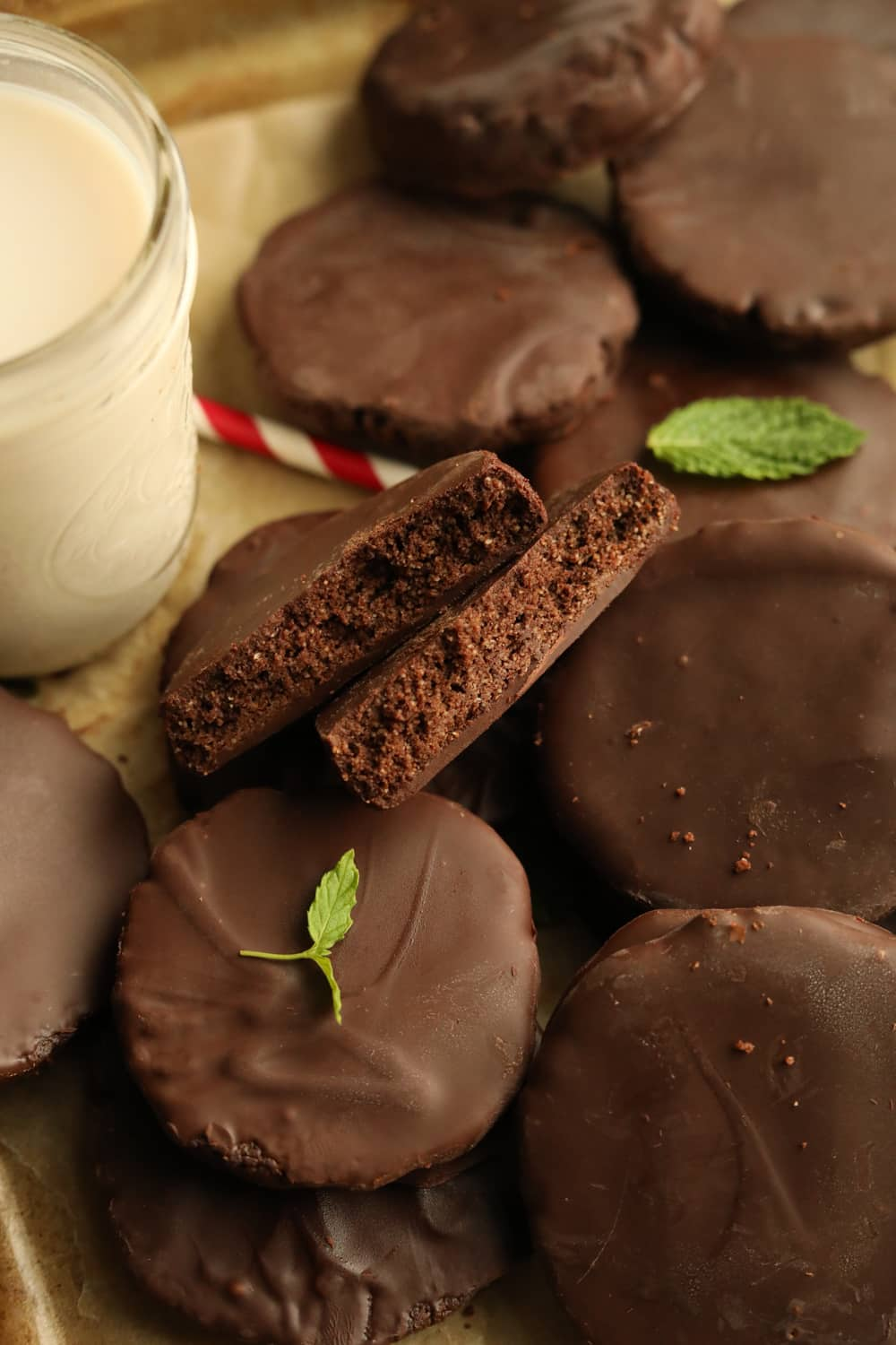 A chocolate cookie broken in half and stacked on other chocolate cookies. There's a glass of milk, a straw, and mint leaves next to the cookies.