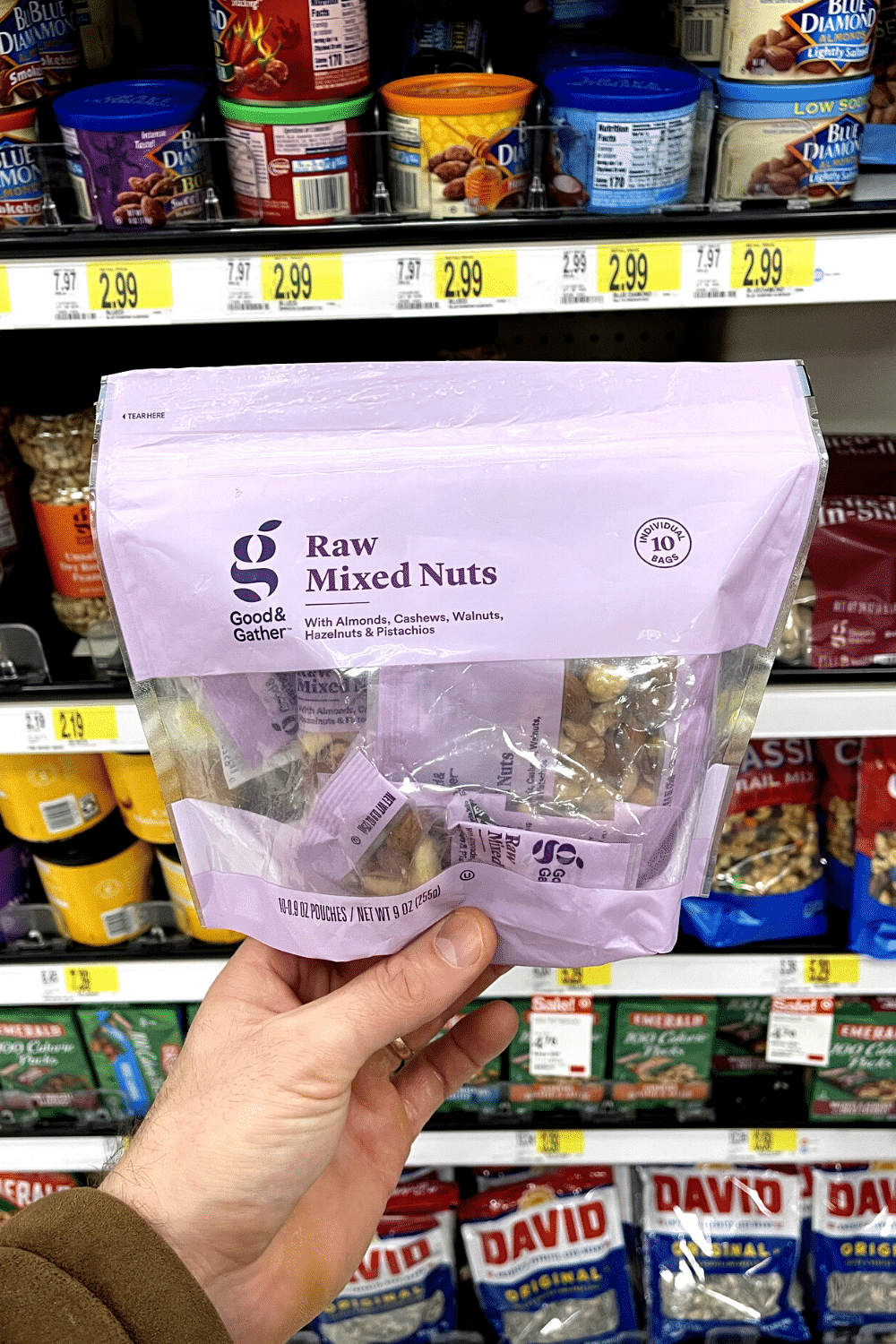 A hand holding a package of raw mixed nut snack packs.