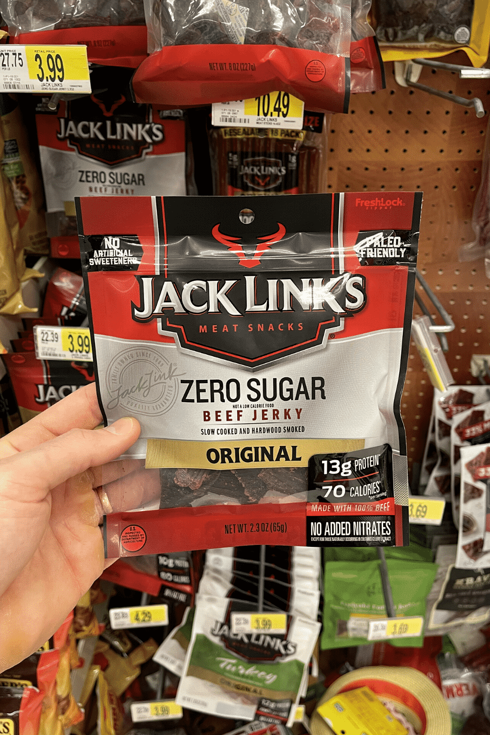 A hand holding a bag of sugar free jerky.