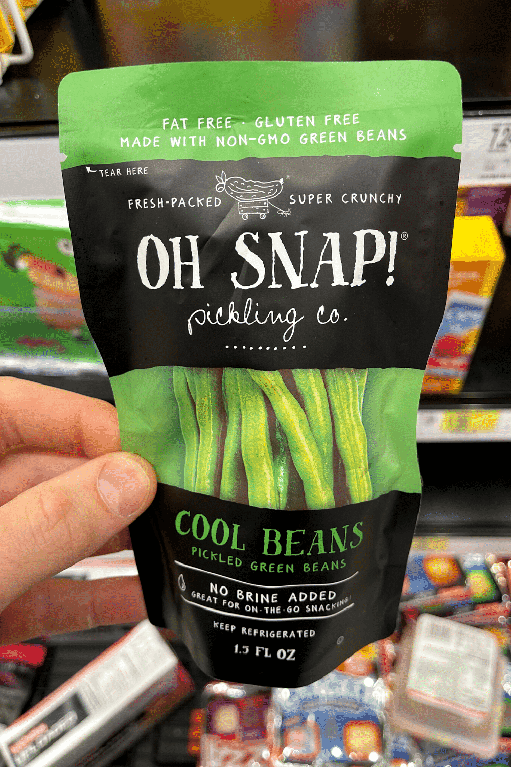 A hand holding a bag of pickled green beans.