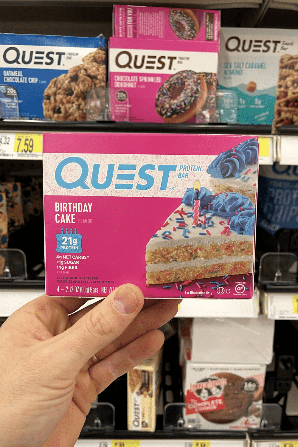 A hand holding a box of low carb birthday cake protein bars.