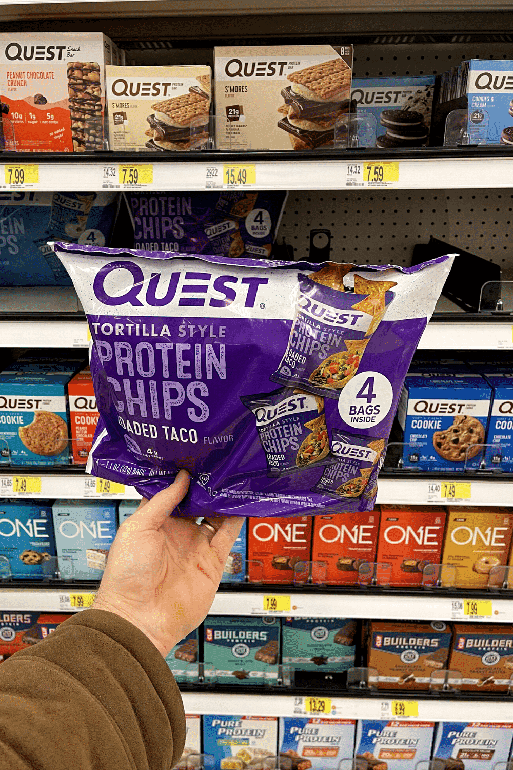 A hand holding a bag of of protein chips.