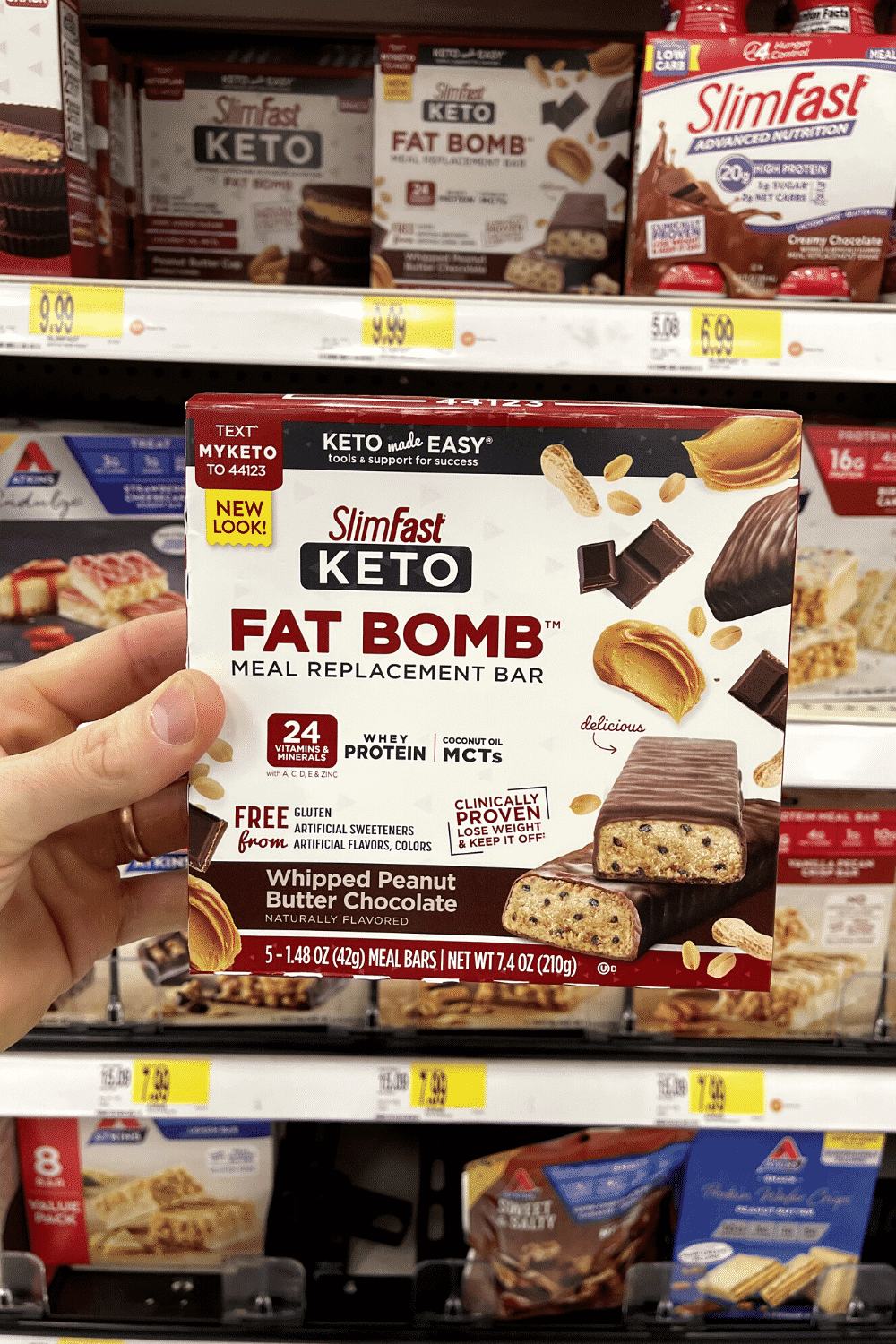 A hand holding a box of keto meal replacement bars.