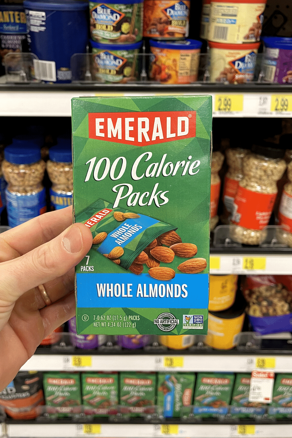 A hand holding a box of almond snack packs.