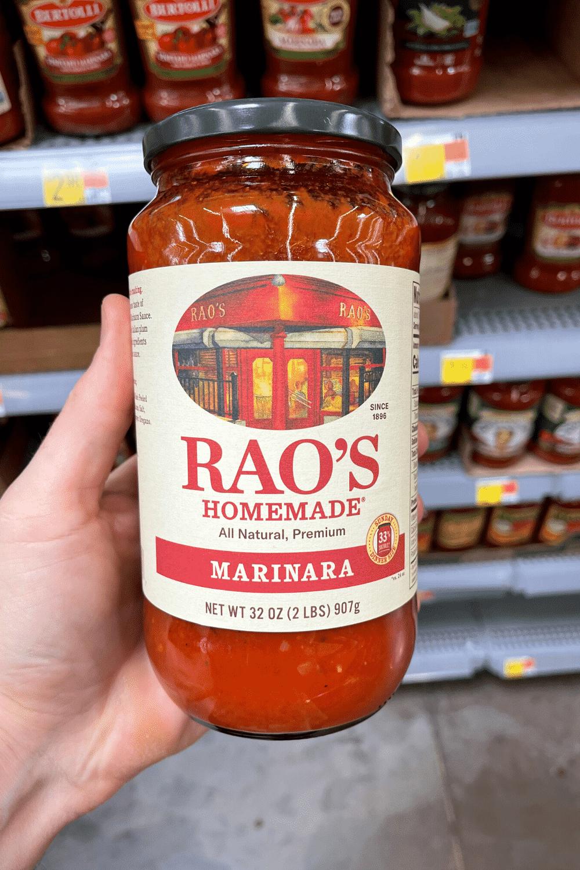 A hand holding a jar of marinara sauce.