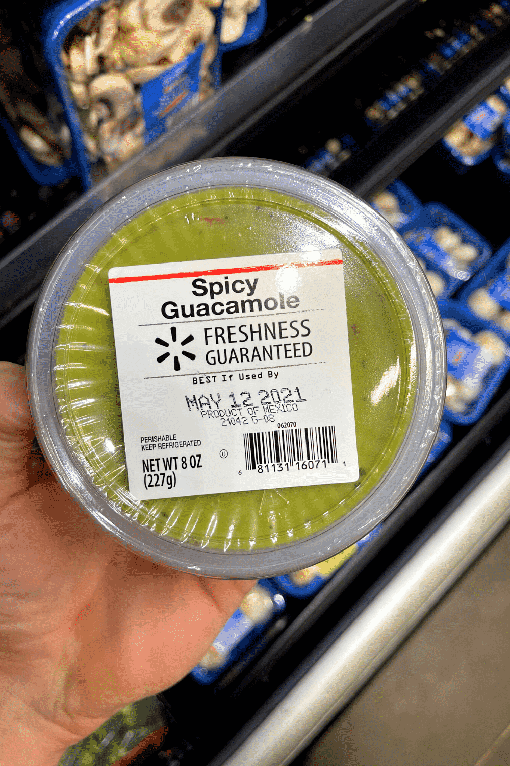 A hand holding a container of guacamole.
