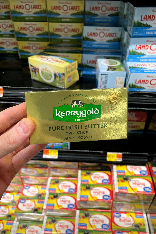 A hand holding a box of Irish butter.