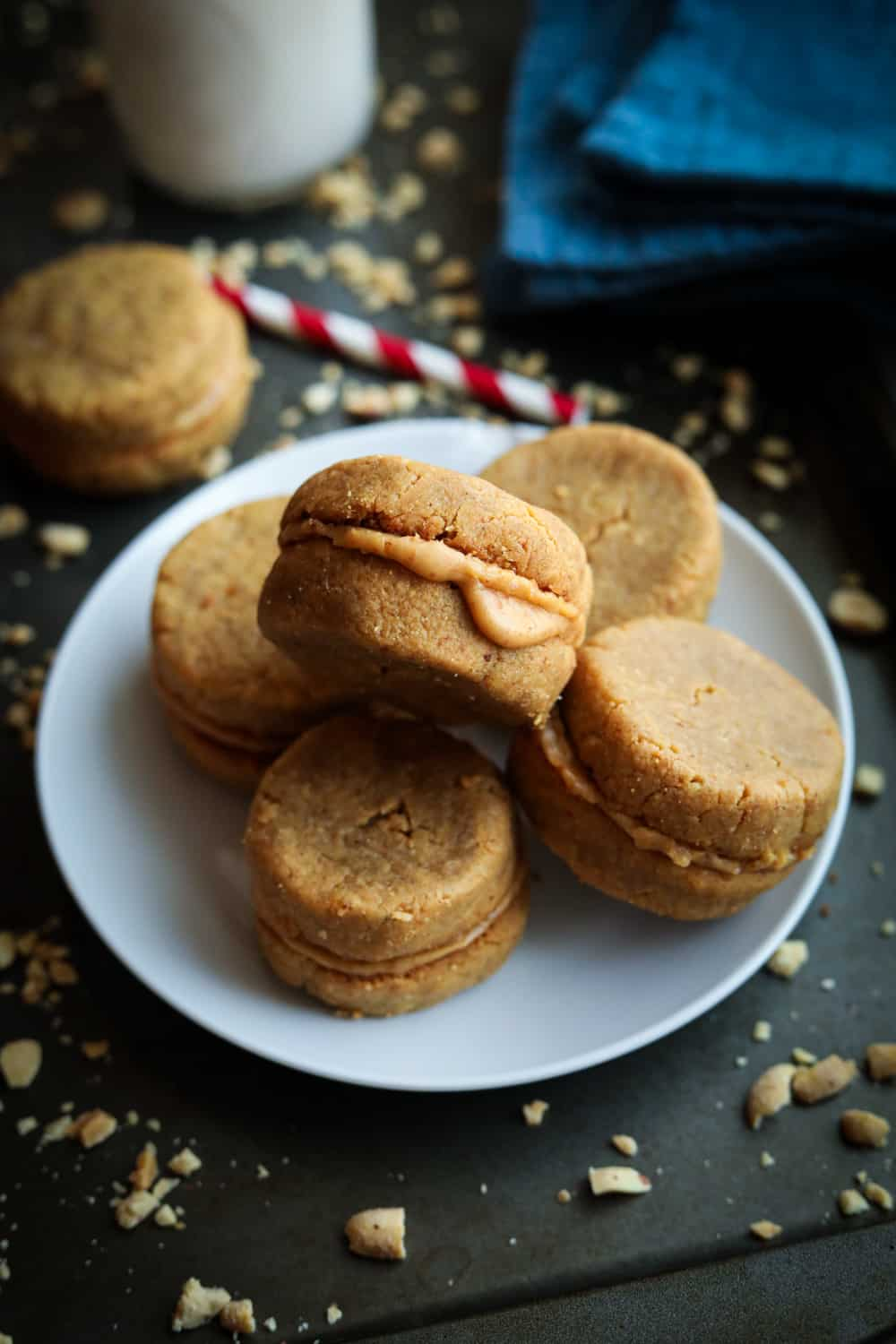 A white plate with 5 peanut butter cookies on it. The plate is set on a baking sheet with a glass of milk, and a blue napkin behind it.