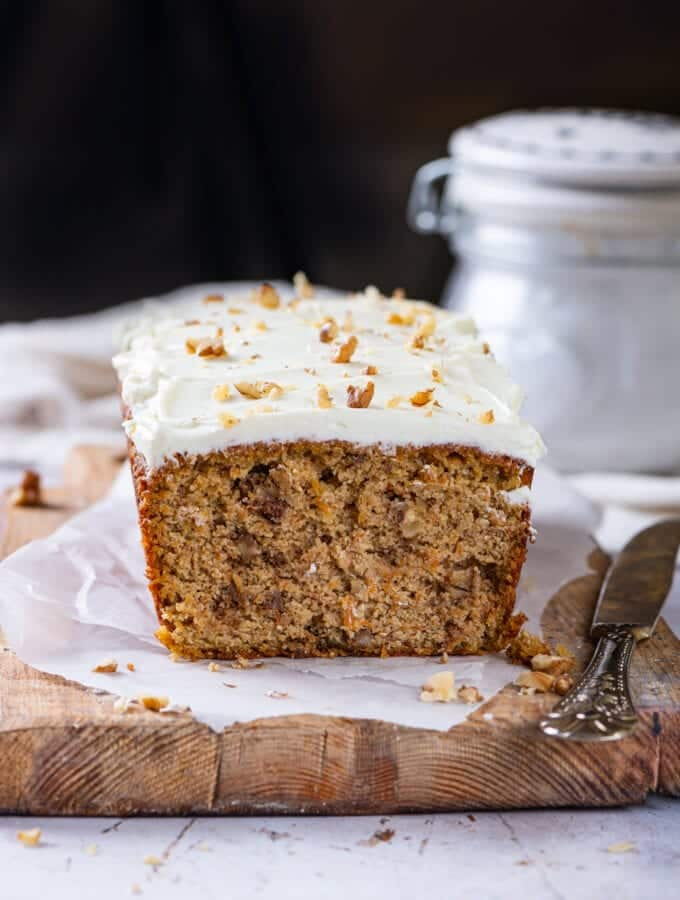 A loaf of carrot cake on a cutting board line with parchment paper.