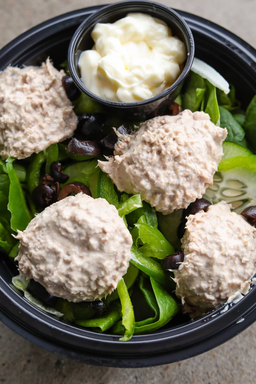 A black bowl filled with green vegetables, four scoops of tunafish that's mixed with mayonnaise, and a cup of mayonnaise.