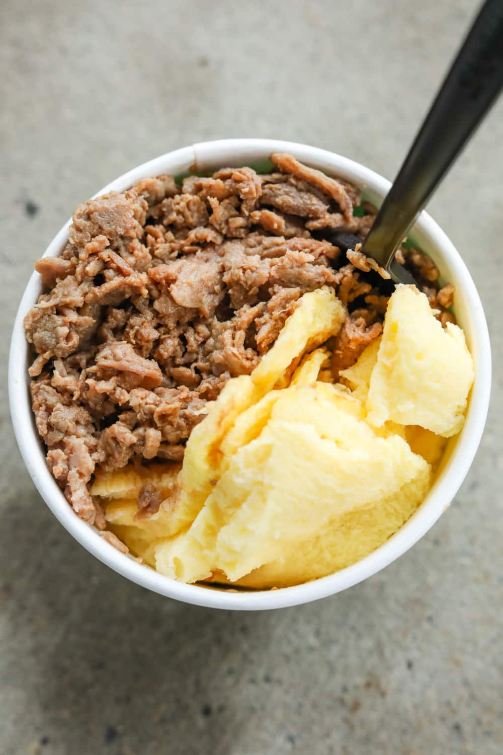 A white cup filled with shredded steak, scrambled eggs, and cheese.