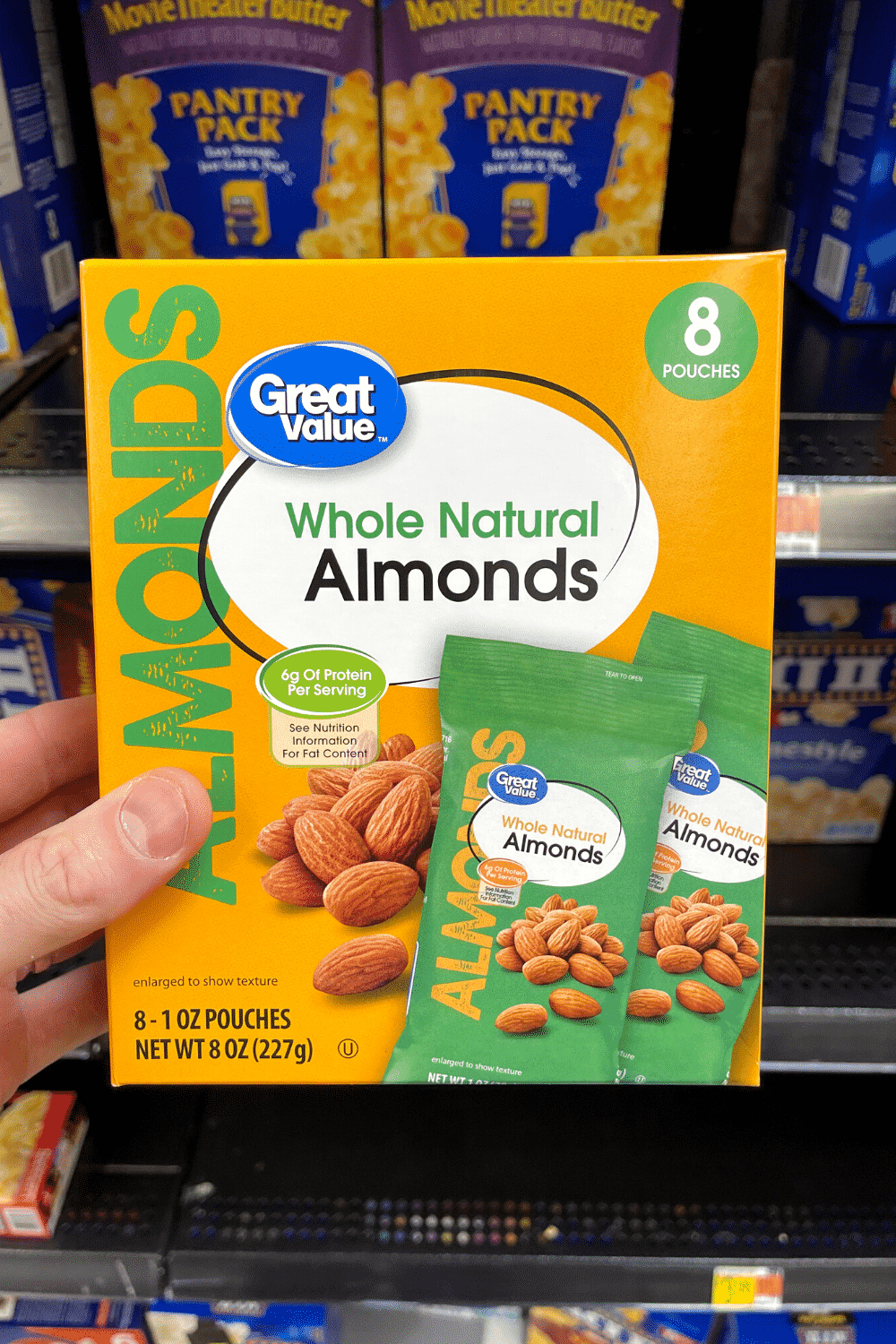 A hand holding a box of raw almond snack packs.