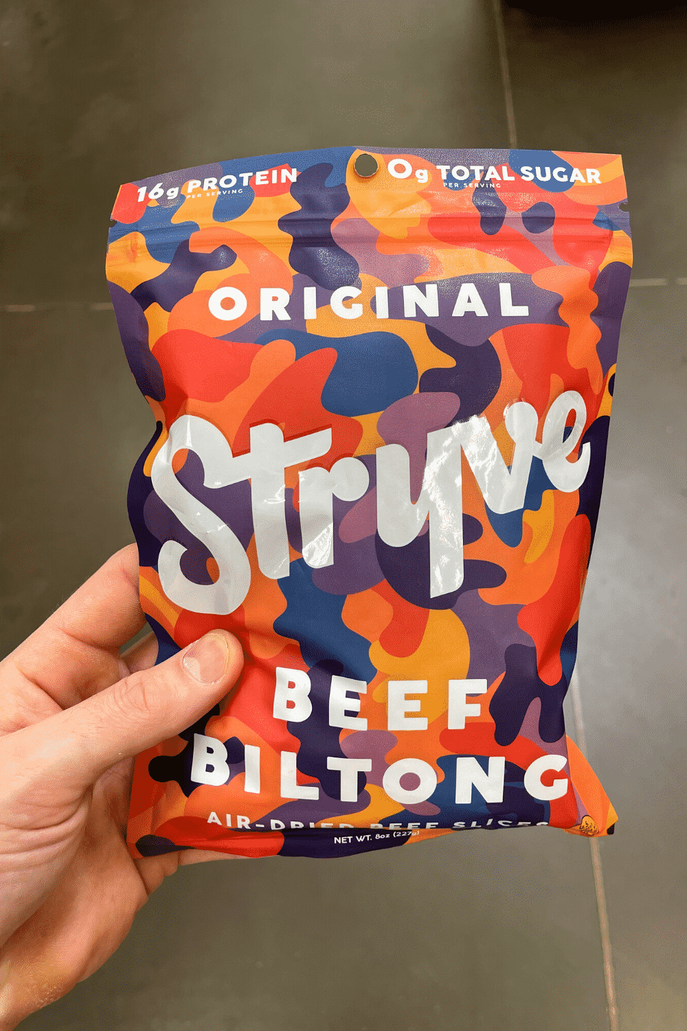 A hand holding a bag of beef biltong.