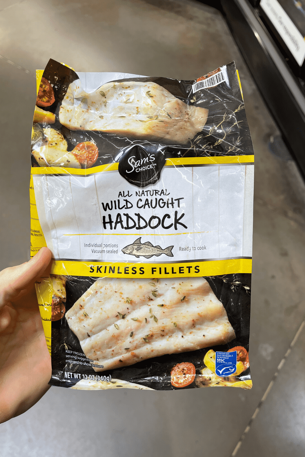 A hand holding a bag of frozen haddock.