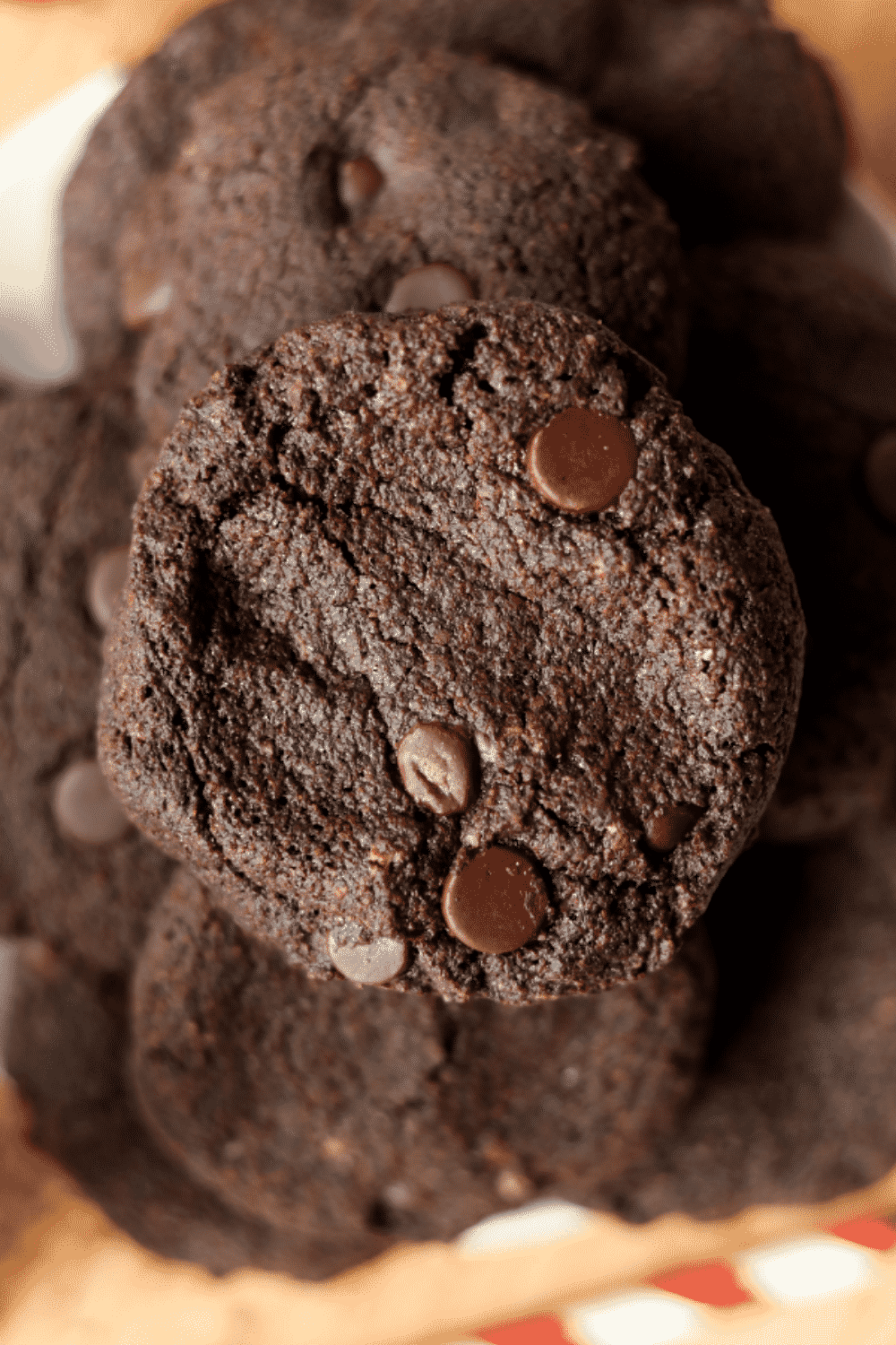 A stack of multiple chocolate cookies with chocolate chips.