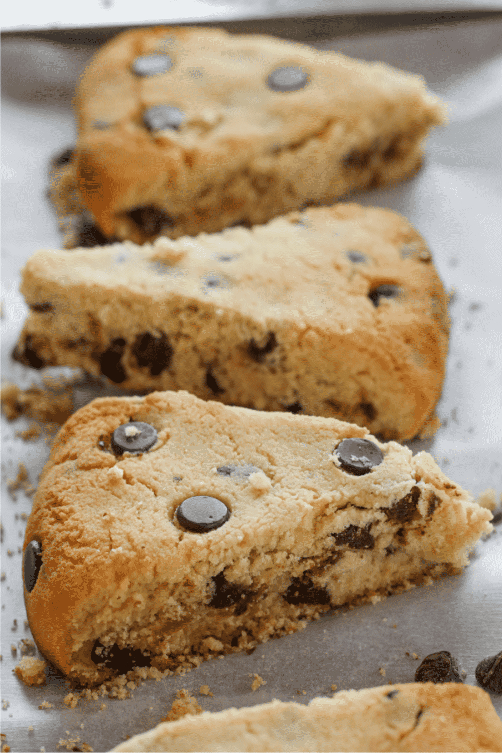 Three chocolate chip scones on a piece of white parchment paper.