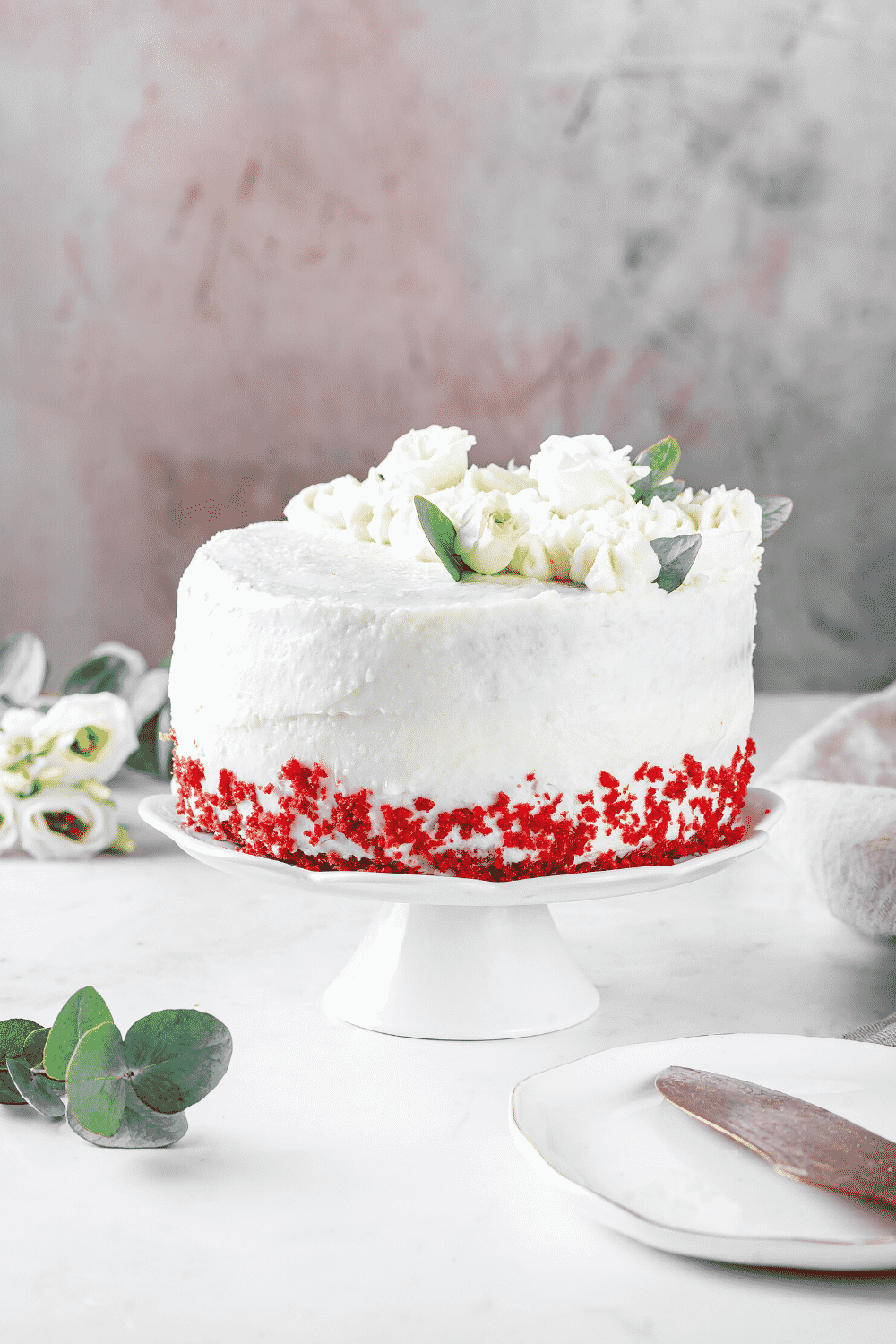 An entire red velvet cake on a white serving tray.