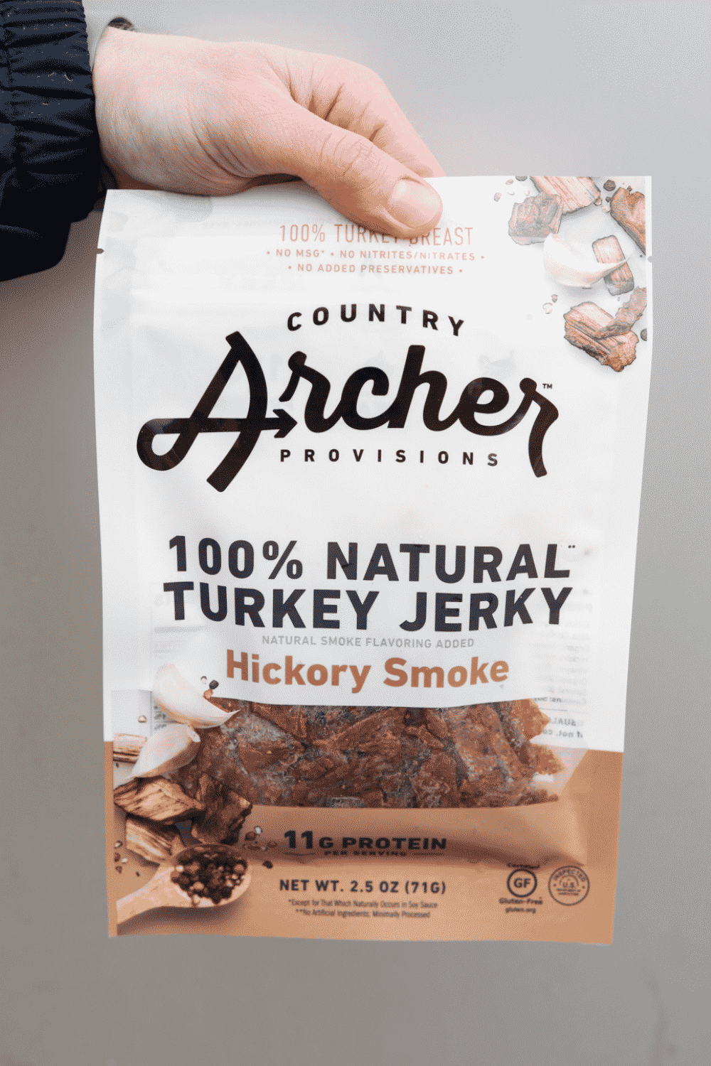 A hand holding a bag of country archer provisions hundred percent natural turkey jerky hickory smoke flavored.
