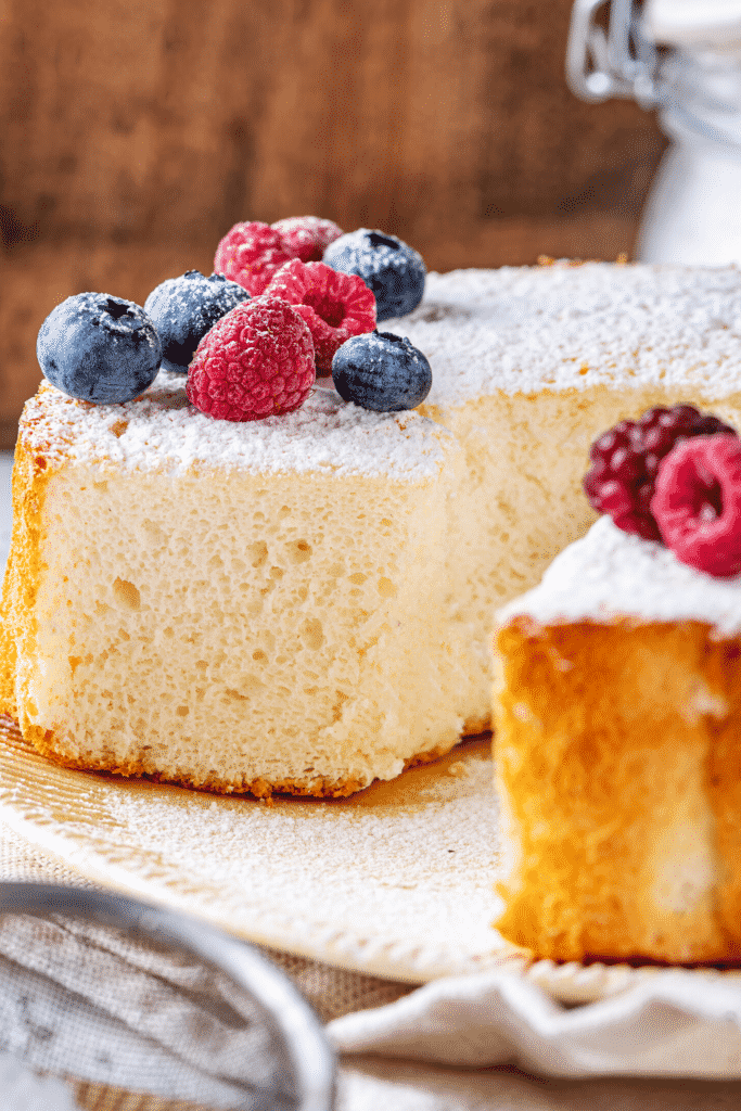 A angel food cake with a slice taken out of the front of the cake.