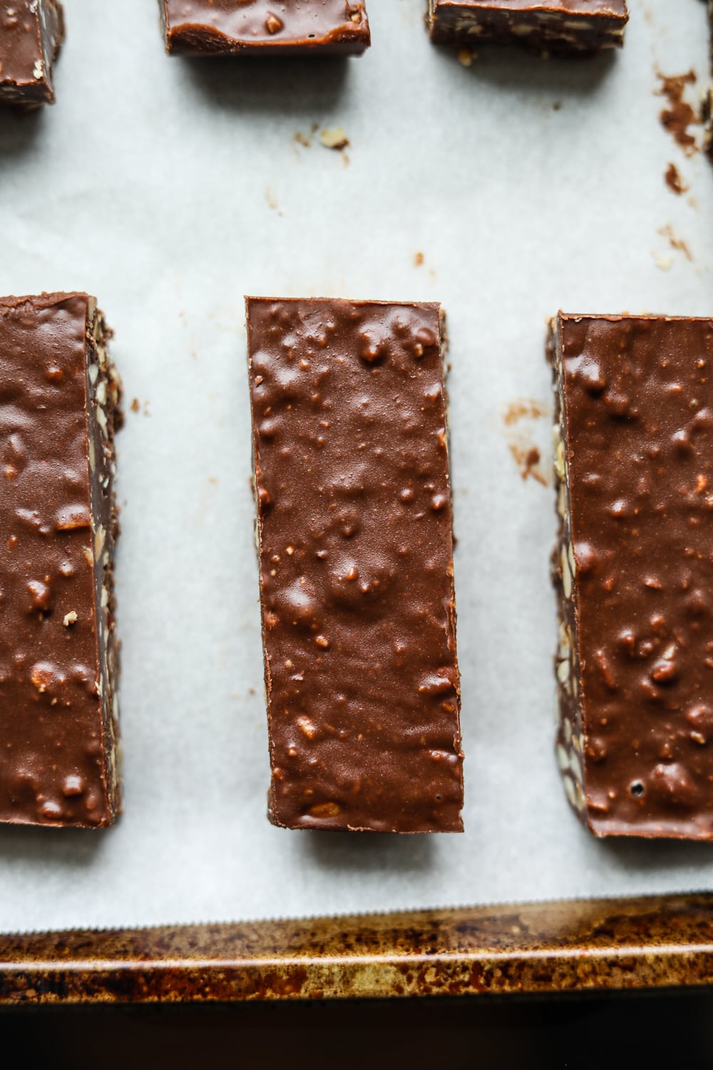 Chocolate candy bars on a baking sheet lined with parchment paper.
