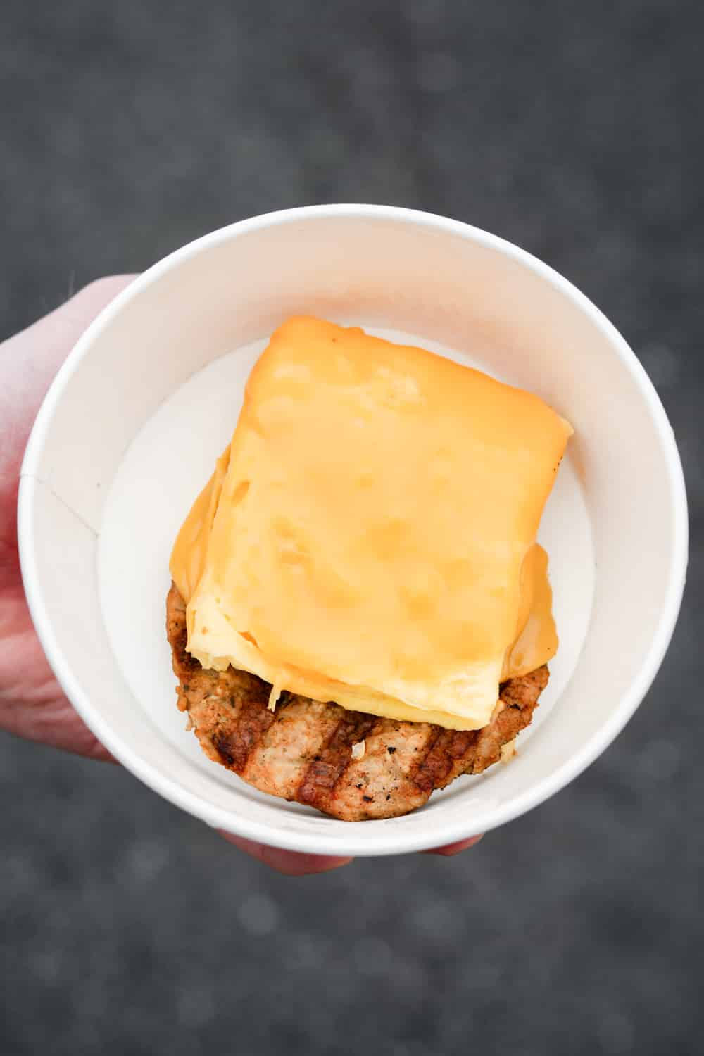 A hand holding a bowl filled with a sausage patty and egg on top and American cheese on the egg.