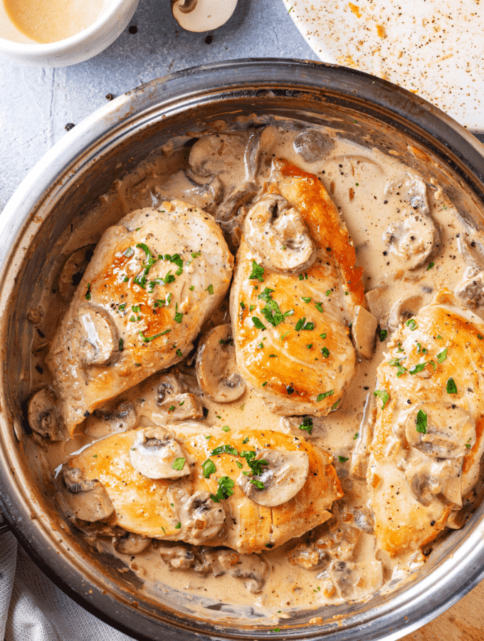 A pan filled with four pieces of chicken marsala. The pan is on a wooden cutting board on a blue counter.