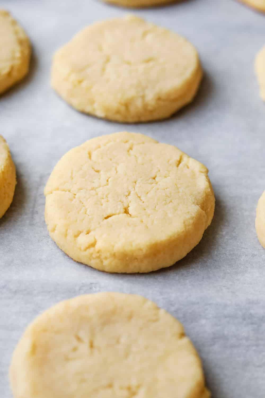 Lemon cookies set on a sheet of parchment paper.