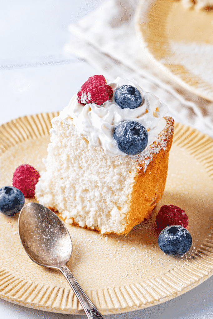 A piece of angel food cake on a plate with a raspberry and blueberry in front of and behind the piece of cake.