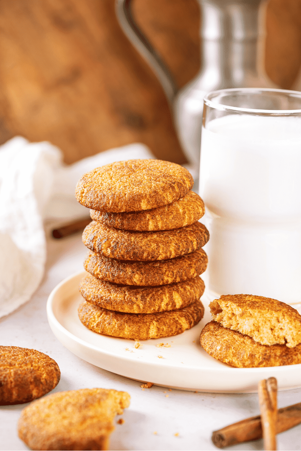 A stack of six snickerdoodle cookies on a white plate. There is a whole snickerdoodle cookie and half of one on top of it to the right of the stack. Behind that is a glass of milk.