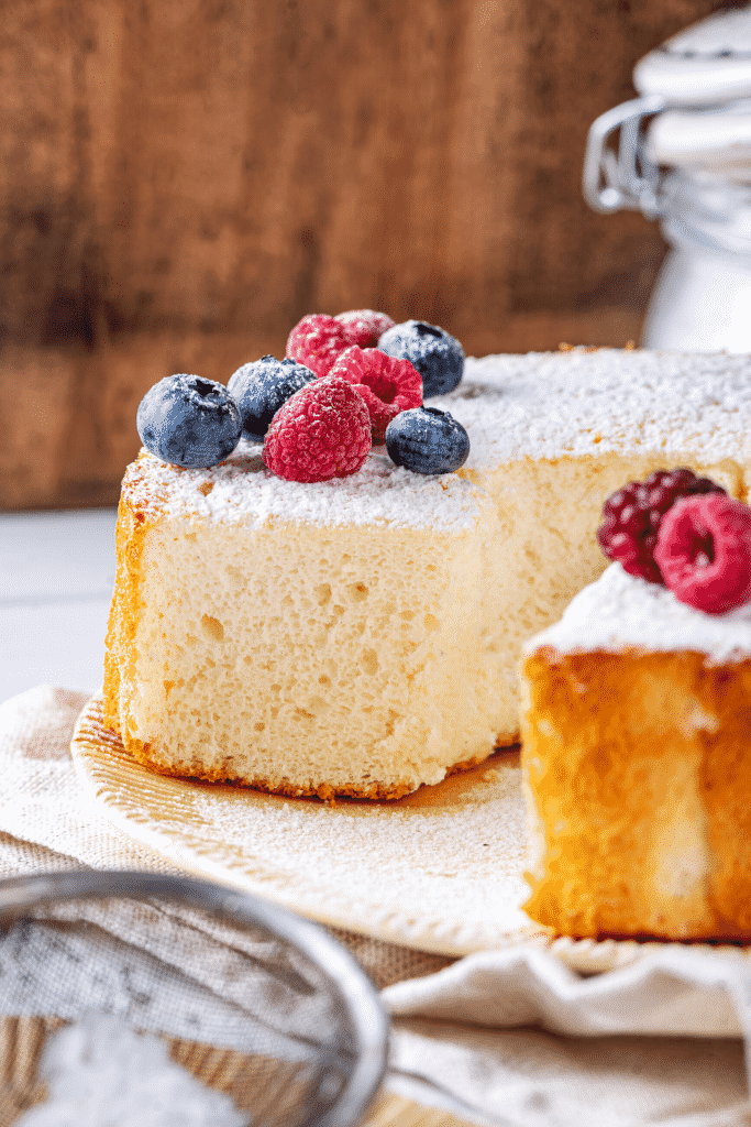 An angel food cake on a plate with two slices taken out of the front of the cake