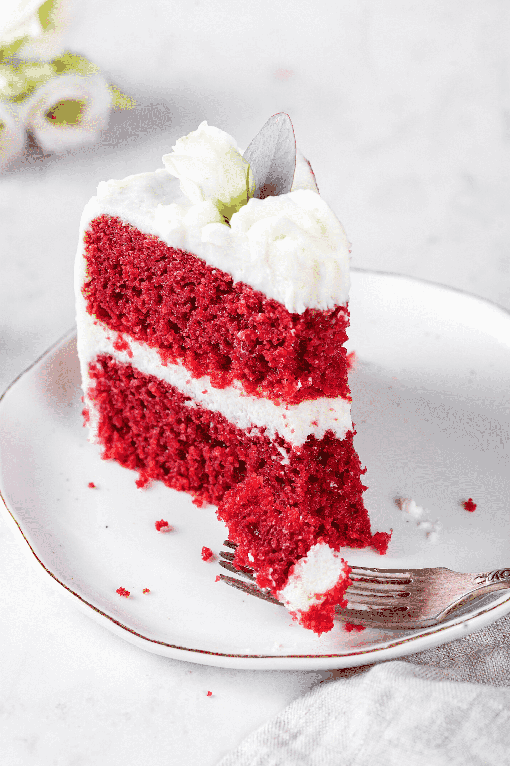 A piece of red velvet cake on a white plate. A fork is in front of the cake with a piece of cake on it.