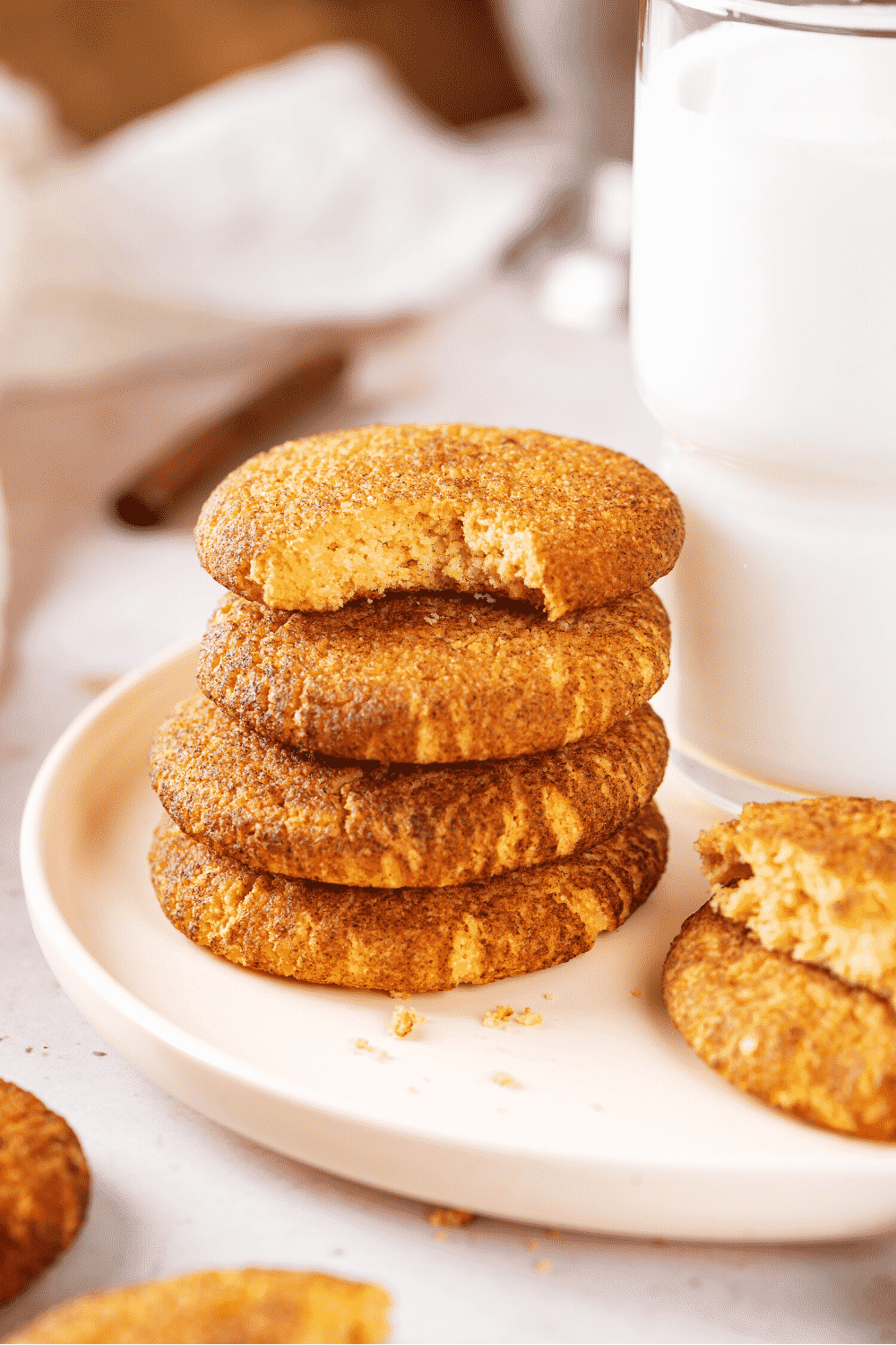 A stack of four snickerdoodle cookies on a white plate. The top cookie has a bite out of the front of it and there is a glass of milk directly to the right of the stack.