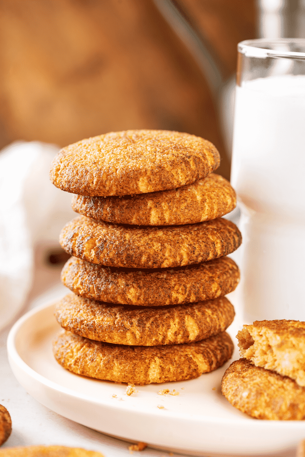 A stack of six snickerdoodle cookies on a white plate. A glass of milk is to the right of the stack.