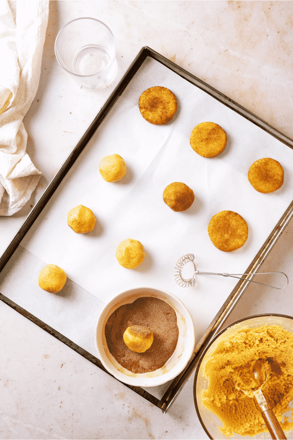 A baking sheet lined with parchment paper with with rows of snickerdoodle cookies on it. A few snickerdoodle cookies are rolled in cinnamon sugar coating and flattened and a few are still a dough ball. There is a bowl of cinnamon sugar on the parchment paper with one cookie in it.